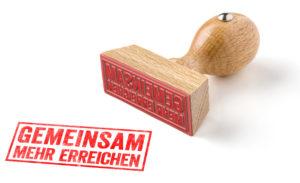 EIn Holzstempel liegt neben einem roten Stepelabdruck 'Gemeinsam mehr erreichen'