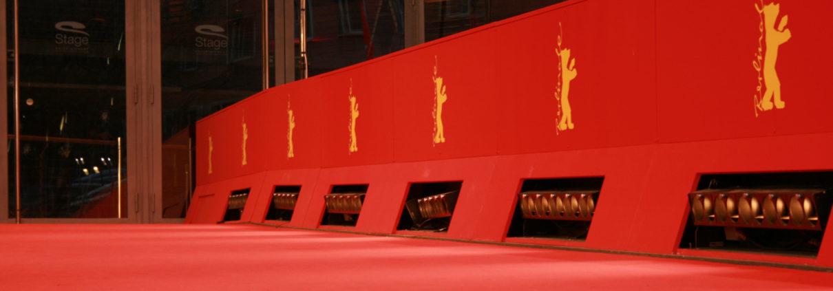 Neben einem roten Teppich verläufteine rote Bande mit dem golden Berlinale-Bären-Logo