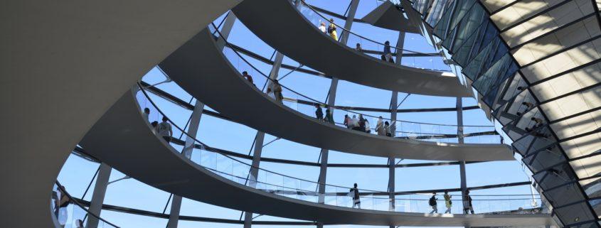 Zwischen den geschwungenem Aufgang in der Reichtagskuppel leuchtet der blaue Himmel durch die rechteckigen Fensterelemente