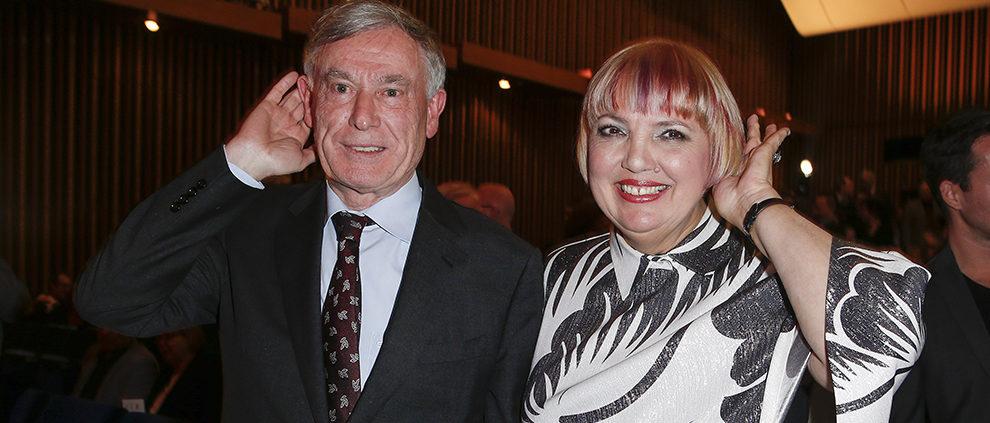 Horst Köhler und Claudia Roth beim 14. Deutschen Hörfilmpreis am 15. März 2016. Sie stehen im dunklen Kinosaal und halten jeweils eine Hand hinter ihr Ohr.