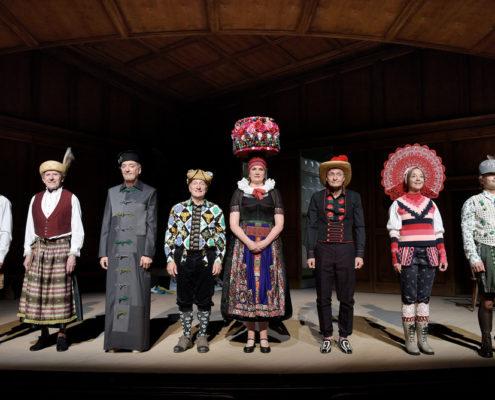 8 Schauspieler stehen in Kostümen an der Bühnenrampe